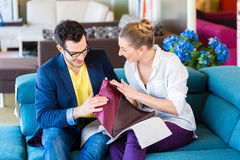 Couple picking couch seat cover in furniture store. Young couple selecting together seat cover for sofa in furniture store Stock Photos