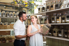 Couple picking herbs and spices in organic store. Joyful young couple choosing herbs and spices in organic food store stock photos