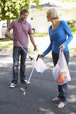 Couple Picking Up Litter In Suburban Street Royalty Free Stock Photos