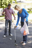 Couple Picking Up Litter In Suburban Street Royalty Free Stock Image
