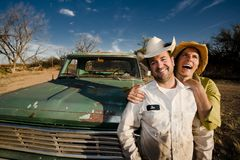 Couple with a Pickup Truck. Man and woman in cowboy hats with old truck Royalty Free Stock Photos