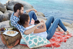 Couple on a picnic at the seaside. Romantic, happy couple during a picnic on the rocks, near the ocean Royalty Free Stock Photography