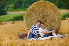 couple picnicking on yellow hay field on summer evening. Stock Image