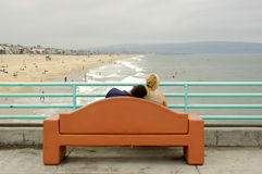 Couple at the pier. Young couple sitting in a bench over the pier. The boyfriend has his head on his girlfriend's shoulder and she is looking away to the right royalty free stock images