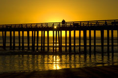 A Couple on a Pier. A couple takes a walk on a pier at a beach Royalty Free Stock Image