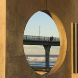 Couple on the pier. This concrete pier looks interesting framed by the round gap in the concrete structure Stock Photo