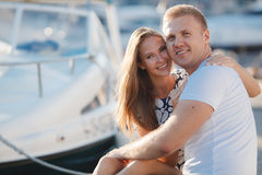 The couple on the pier near the yacht port. Beautiful young couple in love,the guy with the short hair and a girl with long straight blond hair,a beautiful smile royalty free stock photos