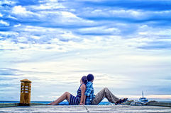 Couple on a pier. A couple sitting back to back on a pier, looking out to sea Royalty Free Stock Photo