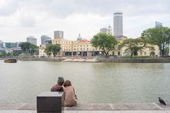 Couple and Pigeon by Singapore River in Late Afternoon Stock Image