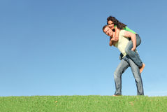 Couple,piggy back. Happy smiling couple outside on grass,piggy back in summer Royalty Free Stock Images