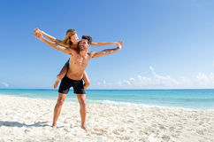 Couple piggy back ride at the beach. Young couple piggy back ride at  the beach Stock Photo
