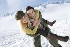Couple piggy back riding in the snow Royalty Free Stock Photography
