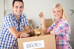 Couple with piggy bank and keys with moving boxes Royalty Free Stock Photo