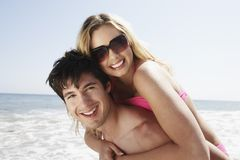 Couple Piggybacking On Beach Royalty Free Stock Photography