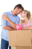 Couple with piggybank over cardboard box Stock Photo