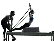 Couple pilates reformer exercises fitness isolated. One caucasian couple exercising pilates reformer exercises fitness in silhouette isolated on white backgound Royalty Free Stock Photos