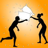 Couple on a pillow fight. Couple having fun pillow fighting with feathers all around and a sunny orange background Stock Images