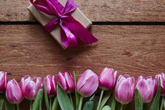 A couple of pink tulips and a wrapped gift for valentines day. Atmosphere spring time easter decoration royalty free stock photography