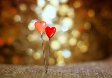A couple of pins in the form of red hearts stuck in the burlap o stock photos