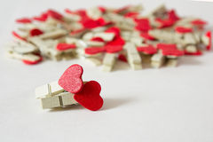 Couple of pins. Wooden pins with red hearts on the white background Royalty Free Stock Photos