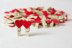 Couple of pins. Wooden pins with red hearts on the white background Stock Photography