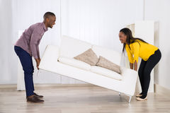 Couple Placing Sofa In Living Room. Young Happy African Couple Placing Sofa In Living Room stock photos