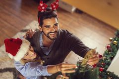 Couple placing a star on the top of the Christmas tree. High angle view of couple in love, wearing Santa hats, decorating Christmas tree, placeing Christmas star royalty free stock photos