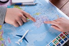 Couple planning trip to Australia, point on map. Couple planning airplane trip to Australia, point on map, top view Royalty Free Stock Image