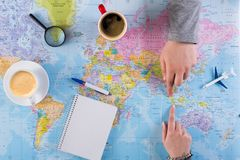 Couple planning trip to Indonesia, point on map. Couple planning airplane trip to Indonesia, point on map, taking notes in blank notebook, copy space stock photography