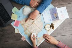 Couple are planning Camino de Santiago in Spain. Table with map and compass and hands from above. Top view. Preparations for the pilgrims` way royalty free stock photography