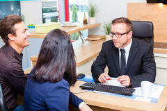 Couple planning kitchen with salesman store. Couple planning kitchen with salesman in furniture store royalty free stock photo