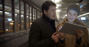 Couple Planning Their Evening with Tablet PC. Young couple is waiting for the tube train. They are using tablet to decide what to do in the evening stock video footage