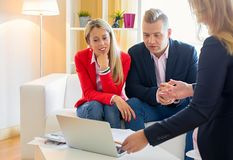 Couple planning their finances together with professional financial adviser stock images