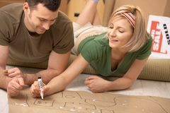 Couple planning their new home. Happy couple planning to furniture the new house after moving in, girl drawing with marker on paper Royalty Free Stock Image