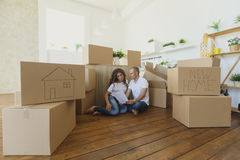 Couple planning their new kitchen siting on the floor. young family moving to a new apartment and carrying boxes Royalty Free Stock Image