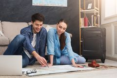 Couple planning trip, studying map at home. Couple planning vacation trip, studying map, sitting on floor at home with laptop, copy space royalty free stock image