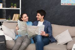 Couple planning trip, studying map at home. Couple planning vacation trip, studying map, sitting at home with packed suitcase, copy space Stock Photos