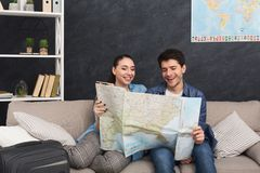 Couple planning trip, studying map at home. Couple planning vacation trip, studying map, sitting at home with packed suitcase, copy space Royalty Free Stock Image