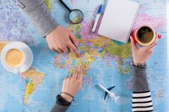 Couple planning trip to Africa, point on map. Couple planning airplane trip to Africa, point on map, taking notes in blank notebook, copy space Royalty Free Stock Photo