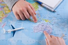 Couple planning trip to Australia, point on map. Couple planning airplane trip to Australia, point on map, top view Stock Images