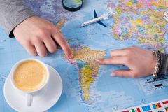 Couple planning trip to Brazil, point on map. Couple planning airplane trip to Brazil, point on map, taking notes in blank notebook, copy space royalty free stock photography