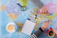 Couple planning trip to China, point on map. Couple planning airplane trip to China, point on map, taking notes in blank notebook, copy space stock photos