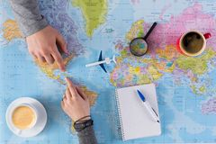 Couple planning trip to Cuba, point on map. Couple planning airplane trip to Cuba, point on map, taking notes in blank notebook, copy space stock images