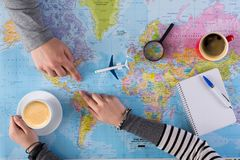 Couple planning trip to Dominican, point on map. Couple planning airplane trip to Dominican Republic, point on map, taking notes in blank notebook, copy space stock photography