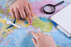 Couple planning trip to India, point on map. Couple planning airplane trip to India, point on map, taking notes in blank notebook, copy space royalty free stock image