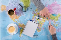 Couple planning trip to India, point on map. Couple planning airplane trip to India, point on map, taking notes in blank notebook, copy space stock image