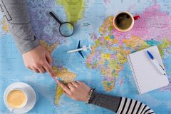 Couple planning trip to Peru, point on map. Couple planning airplane trip to Peru, point on map, taking notes in blank notebook, copy space stock images