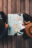 Couple planning vacation sitting by the world map. Stock Photography