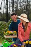 Couple planting flowers in garden. Young couple planting flowers in garden, vertical Royalty Free Stock Photo