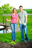 Couple planting a tree. Young smiling people planting the tree outdoor Stock Photo